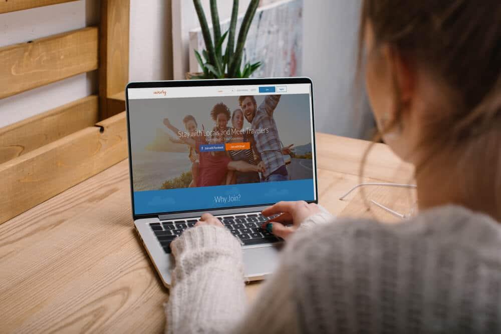 mulher com portátil navega no site do couchsurfing