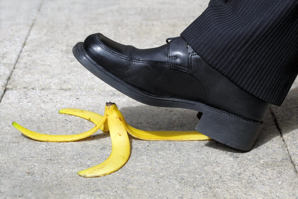casca de banana no chao e sapato preto a pisá-la