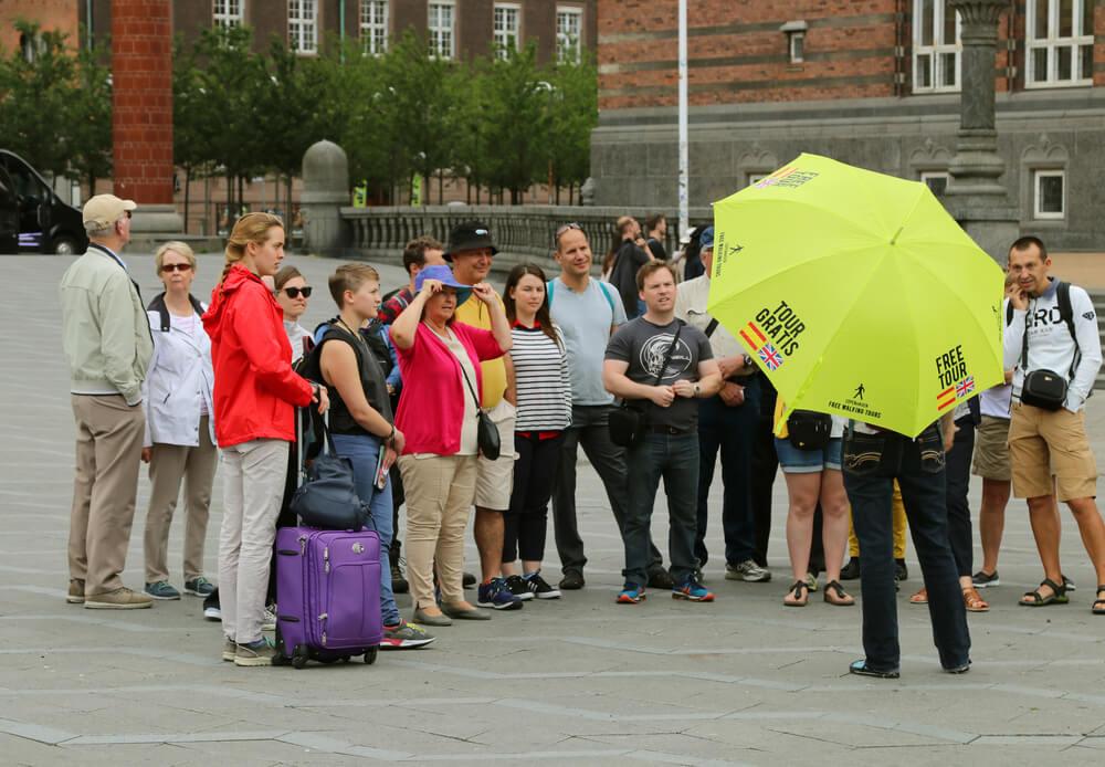 grupo de pessoas assiste às explicações de um guia freetour