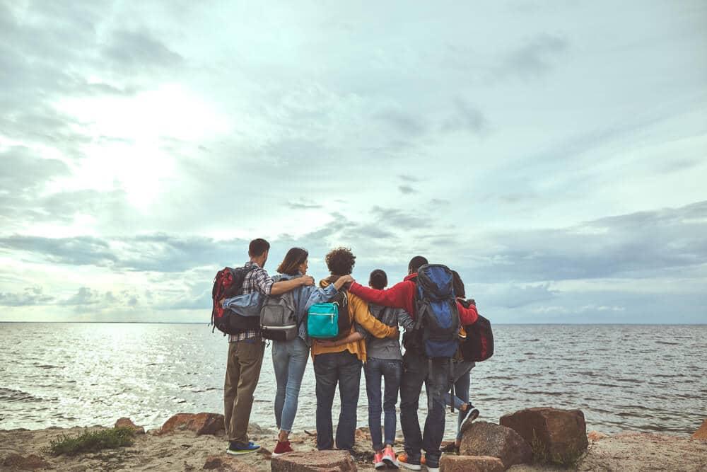 grupo de amigos tira foto de costas enquanto observa o mar