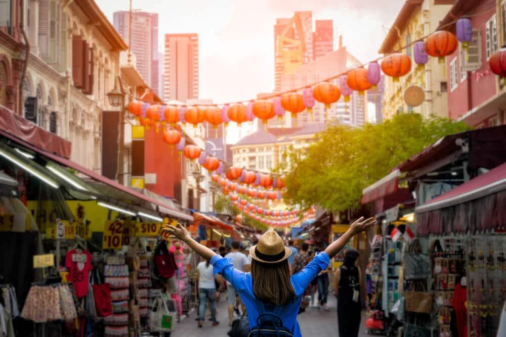 mulher de braços abertos no meio de chinatown