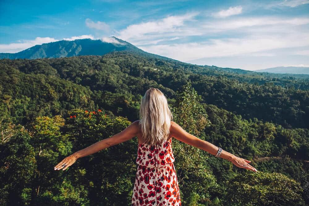 mulher de vestido vermelho e braços abertos contempla a floresta de bali