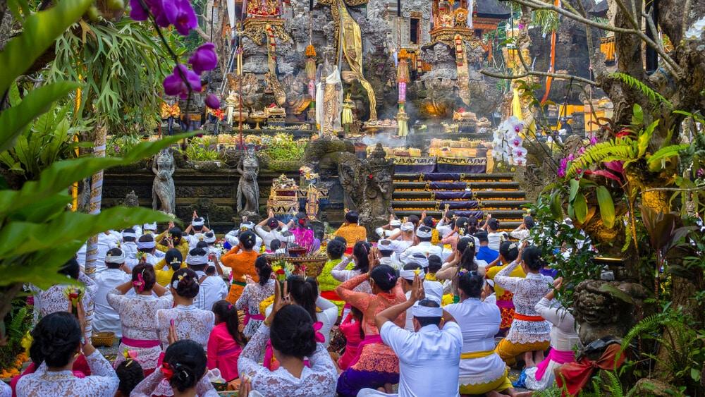 varias pessoas rezam num templo hindu de bali