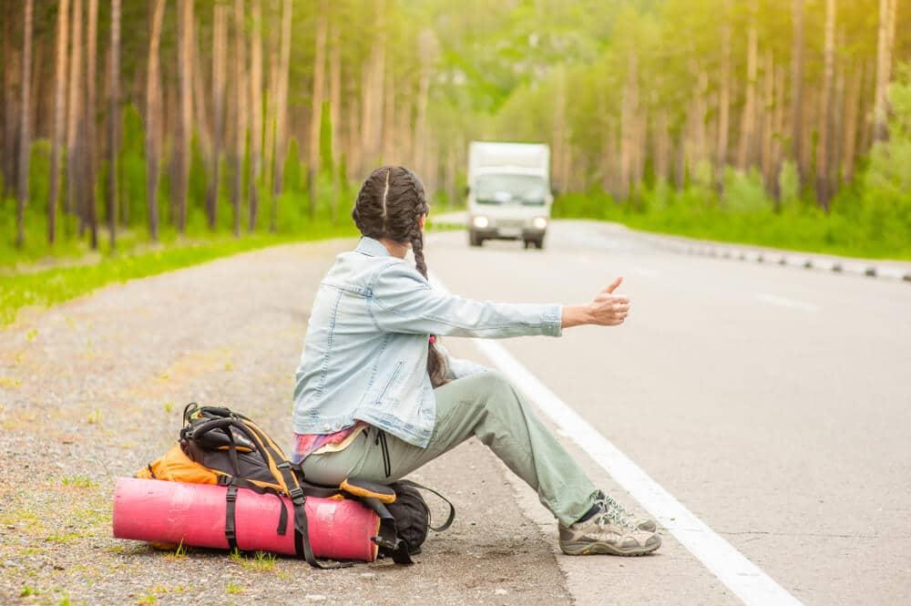 rapariga com tranças pede boleia ao pé de uma estrada