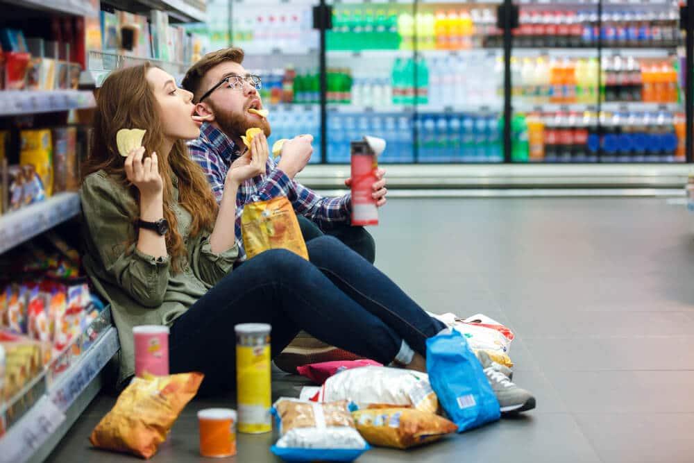 dois jovens comem batatas fritas no corredor de um supermercado