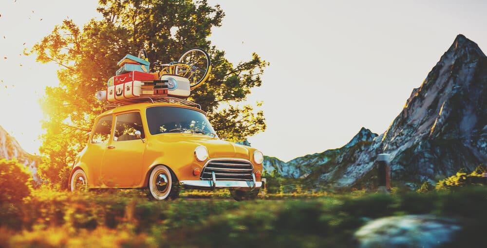 carro antigo amarelo com bagagens no teto