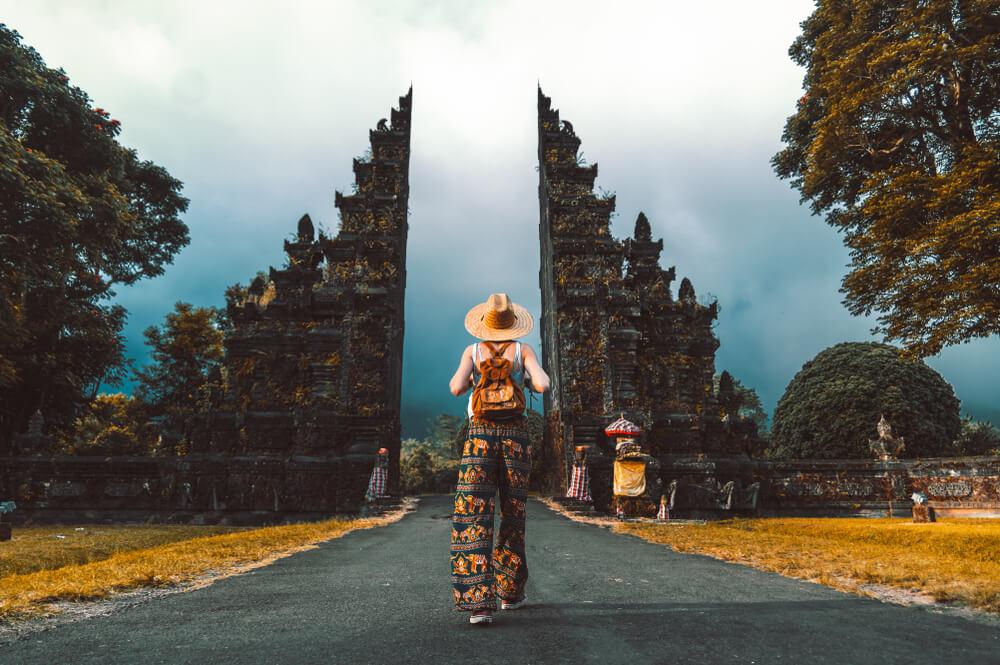 mulher de vestido e chapeu caminha num templo hindu