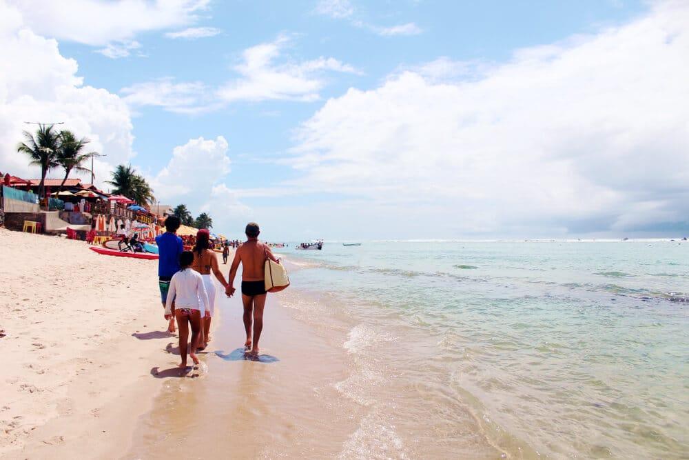 familia passeia por uma praia de Maceió