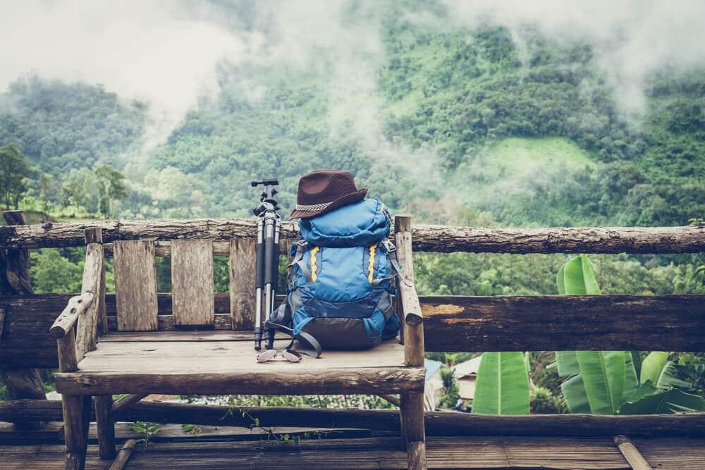 mochila e tripe pousados em cima de um banco