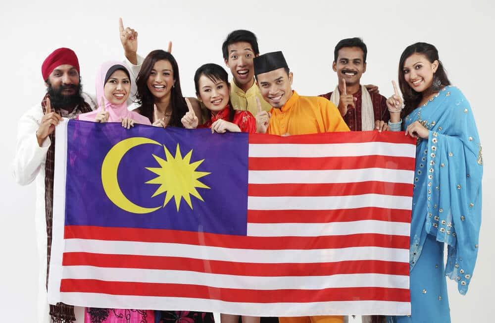pessoas de varias descendencias seguram uma bandeira da malasia