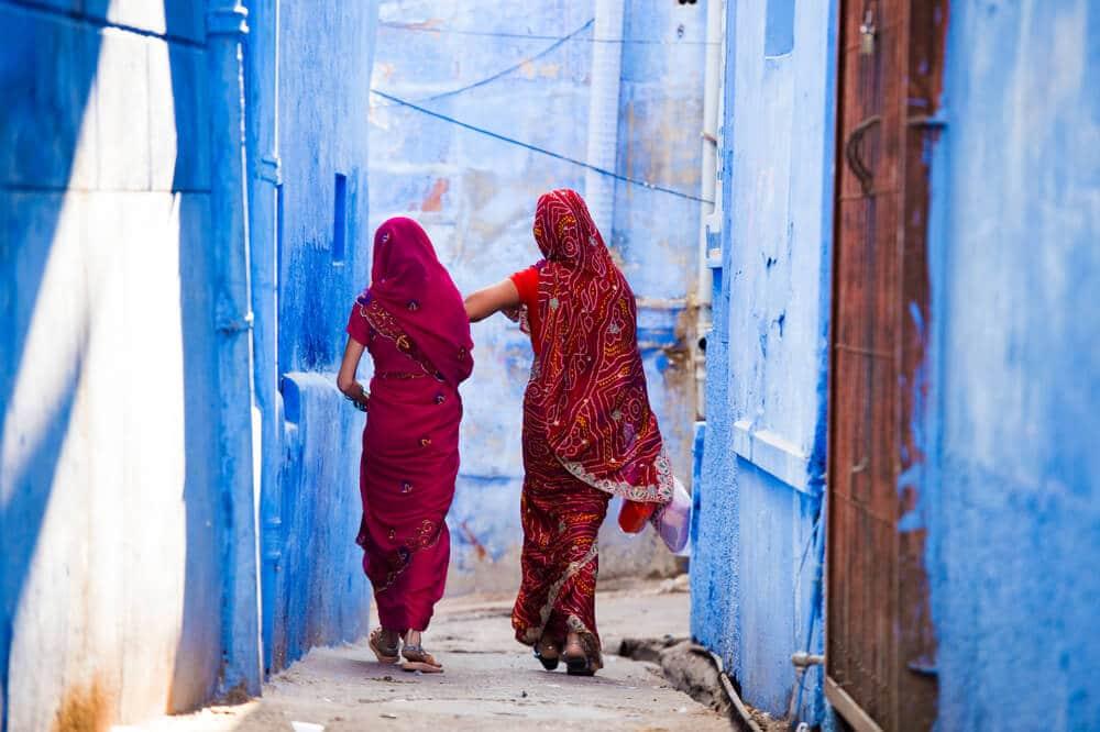 duas mulheres indianas caminham numa rua estreita