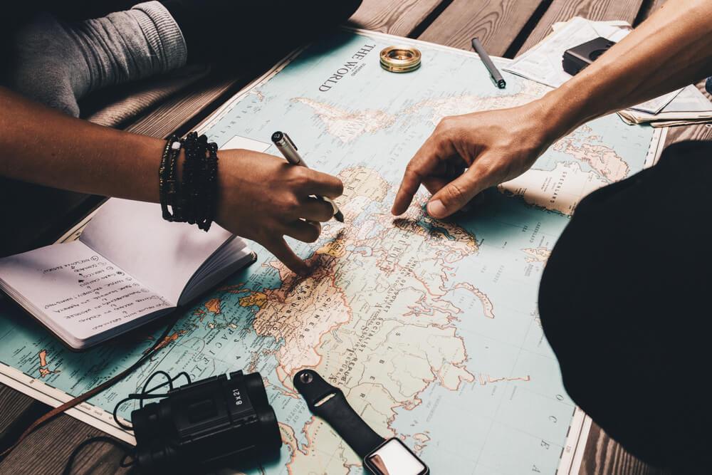 dois amigos planeiam uma viagem com um mapa mundo